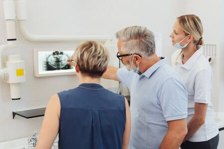 Dentist explaining options to a female patient pointing to an x-ray on a monitor watched by his dental nurse