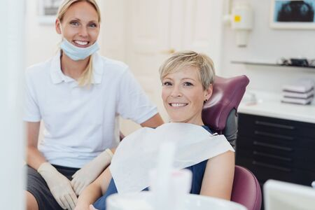 Happy female patient posing together with her woman dentist in the surgery during an examination