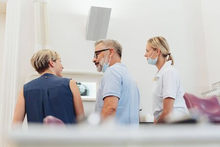 Dentist talking to a patient in his surgery after showing her an x-ray of her teeth watched by his dental nurse
