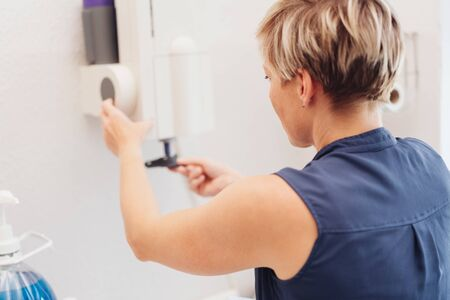 One blond woman in dark blue vest pulling unidentifiable material out of white dispenser on plain wall