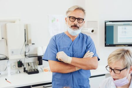 Senior dentist looking thoughtfully at the camera with folded arms as he stands with his assistant in the surgery Stock Photo