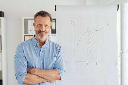 Friendly relaxed man with folded arms and copy space on a white lateral wall standing smiling quietly t the camera