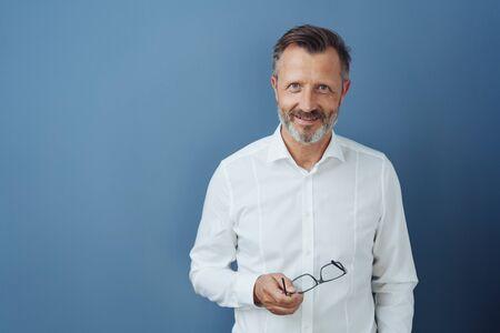 Hombre de mediana edad relajado y amistoso sosteniendo anteojos en la mano mientras sonríe a la cámara contra un fondo de estudio azul con espacio de copia Foto de archivo