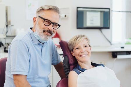 Smiling dentist with a happy woman patient on the examination couch in his surgery in a close up view posing together Stock Photo