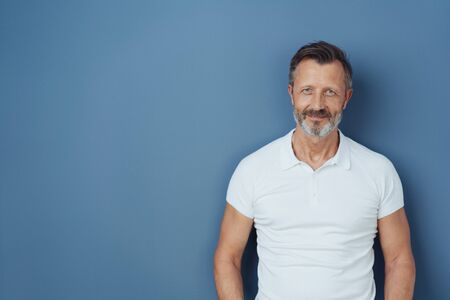 Casual bearded middle-aged man in a casual white t-shirt standing smiling at the camera against a blue studio background with copy space Stock Photo