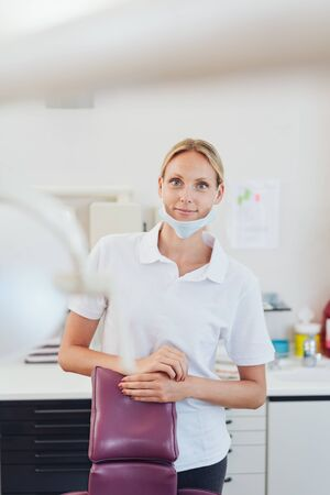 Smiling friendly young dental nurse or assistant waiting in the surgery for the next patient
