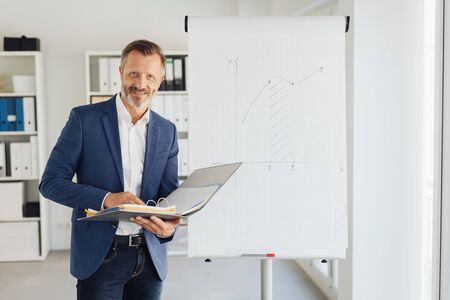 Attractive stylish businessman doing a presentation standing in front of a flip chart holding an open binder with a smile 스톡 콘텐츠
