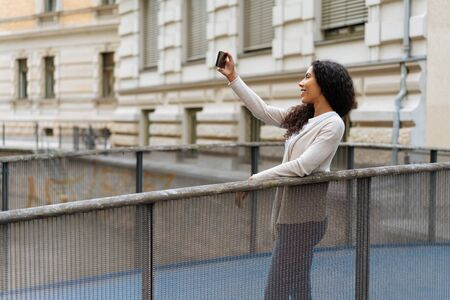 Smiling young woman taking a selfie in town on her smartphone as she poses on a bridge over a canal with copy space