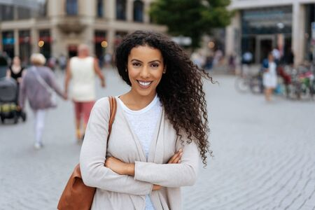 Happy trendy vivacious young African woman standing in an urban square smiling at the camera with folded arms Archivio Fotografico