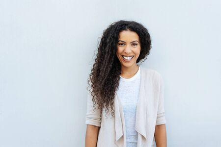 Attractive young woman with long curly dark hair posing in front of a white wall smiling happily at the camera with copy space