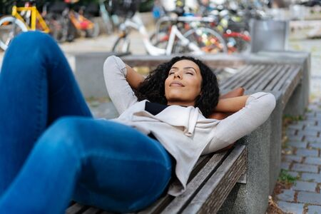 Tired young woman relaxing lying on an urban bench on the sidewalk of a quiet back street with her eyes closed and blissful smile Reklamní fotografie