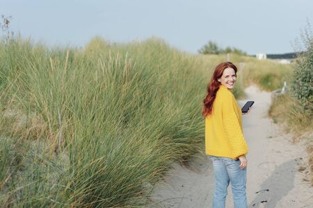 Happy young woman walking along a sandy coastal footpath carrying a mobile phone and looking back at the camera smiling