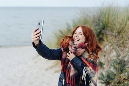 Laughing young woman wearing a warm winter scarf taking a selfie on a mobile phone as she enjoys a day of autumn sunshine on a tropical beach and dunes