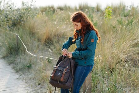 Young woman backpacker rummaging in her backpack as she rests on a wooden pole along a coastal boardwalk in early autumn sunshine