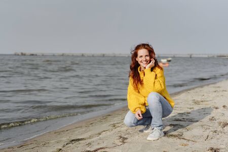 Friendly happy young woman crouching on a sandy beach at the edge of a calm ocean looking at the camera in autumn sunshine Banco de Imagens