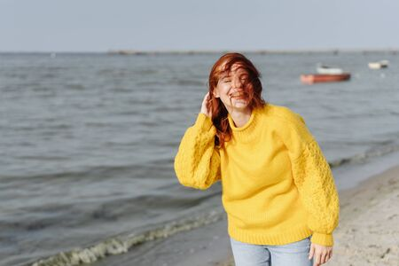 Happy vivacious young woman giggling and smiling as she tries to stop her long red hair blowing about her face on a sandy tropical beach in autumn