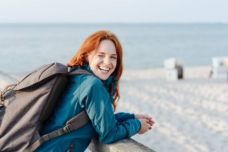 Laughing young woman wearing a backpack with a lovely vivacious smile leaning on a wooden pier overlooking a beach turning to grin at the camera