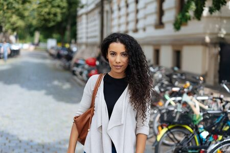 Trendy young woman walking in town passing parked bicycles in a quiet street looking at camera with a thoughtful expression Reklamní fotografie