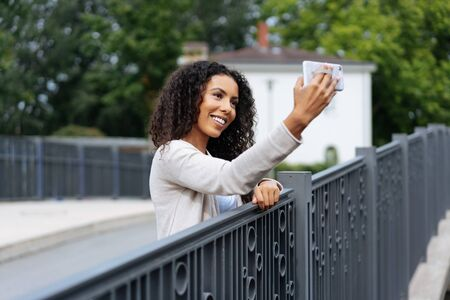 Cute young woman taking a selfie on a bridge with wrought iron railing posing for the camera on her smartphone