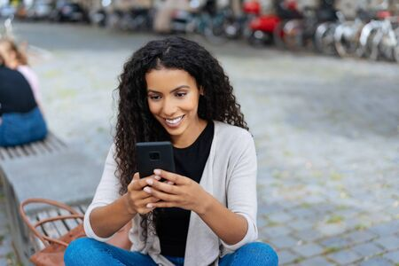Attractive young African Woman relaxing in town on a bench in a quiet street sending a text message on her mobile phone 版權商用圖片