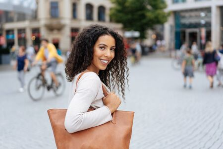 Stylish friendly young woman holding a large handbag looking back over her shoulder at the camera with a smile in an urban street