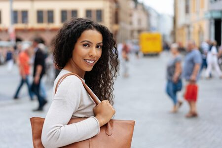 Thoughtful young woman carrying a large handbag turning back in an urban street to look at the camera with a quiet smile
