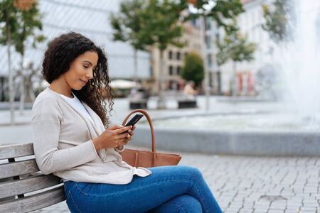 Young woman in jeans relaxing on a bench in town alongside a fountain reading a message on her mobile phone
