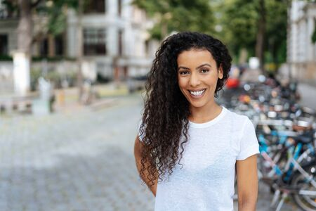 Smiling young woman in a quiet urban street looking at the camera with a beaming smile standing in front of parked bicycles 版權商用圖片