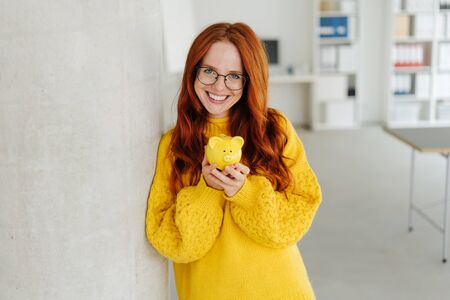 Pretty young redhead woman wearing glasses leaning against a column indoors holding a piggy bank with a sweet smile and copy space 版權商用圖片 - 132112049