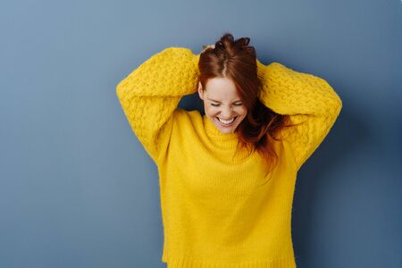 Excited young woman grinning happily looking down with her hands raised to her long red hair over a blue studio background with copy space 版權商用圖片