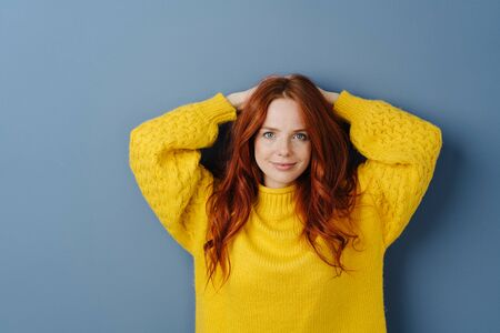 Attractive young red head woman posing with raised arms looking at the camera with a quiet smile over a blue studio background with copy space 版權商用圖片 - 132112059