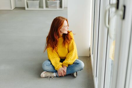 Happy casual young woman sitting cross-legged on the floor looking out of a glass door with a beaming smile in a high angle view 版權商用圖片 - 132112061