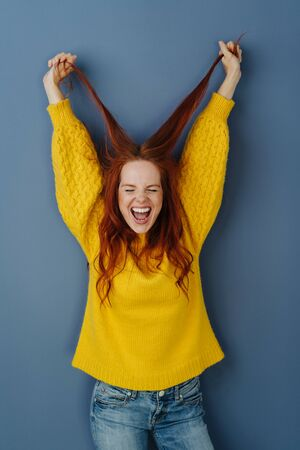 Elated casual young woman cheering and pulling up her long red hair in her hands over a blue studio background