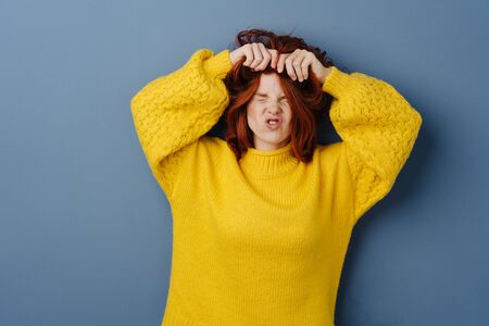 Frustrated angry young woman tearing at her long red hair with a grimace over a blue studio background with copy space