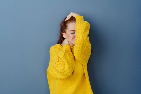 Blissful young woman taking a moment to herself covering her face with her arm as she poses with closed eyes and a beaming smile of pleasure over a blue studio background with copy space 版權商用圖片 - 132112316