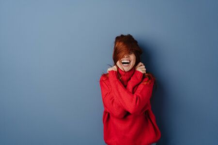 Laughing mischievous young redhead woman pulling her long hair over her face over a blue studio background with copy space