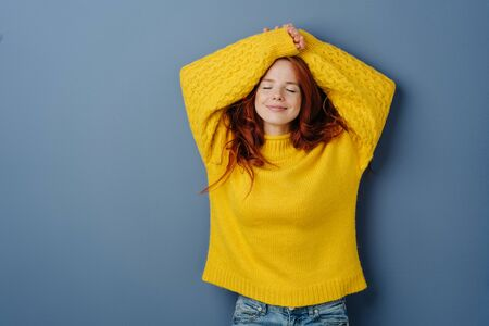 Satisfied happy young woman relaxing with closed eyes and her arms raised above her head with a serene smile over a blue studio background with copy space