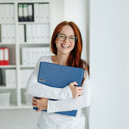 Laughing successful young businesswoman standing in a large airy office clutching a file in her arms grinning at the camera