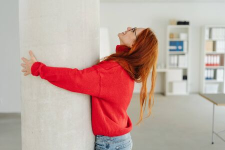 Exuberant young redhead woman hugging an indoor pillar with a happy smile in a large spacious office