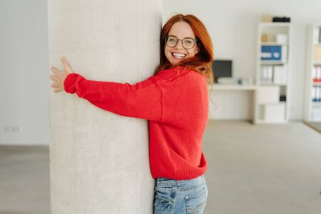 Friendly young woman with a beaming happy smile hugging an indoor pillar in an office with lateral copy space Zdjęcie Seryjne