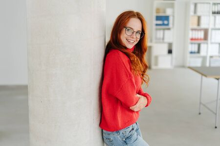 Casual young student or businesswoman standing in red sweater and jeans with folded arms leaning on a pillar in the office grinning at the camera with copy space