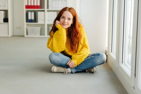Thoughtful casual young woman in jeans and bright yellow woollen sweater sitting cross-legged on the floor indoors with chin on hand staring at the camera