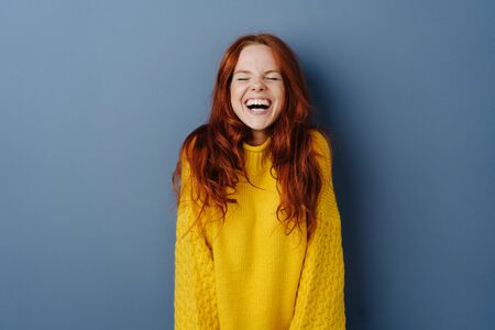 Quirky young woman screwing up her eyes as she enjoys a hearty laugh at a joke over a blue studio background with copy space