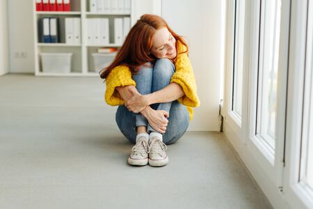 Happy young student sitting on the floor in denim jeans and yellow sweater clutching her knees with a beaming smile alongside glass doors 版權商用圖片 - 132112335