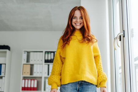 Low angle view of a vivacious young woman in jeans and colorful yellow sweater grinning down at the camera indoors in an office