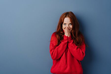 Cute young redhead woman with a shy smile holding her hands to her mouth as she looks at the camera over a blue studio background with copy space Stockfoto