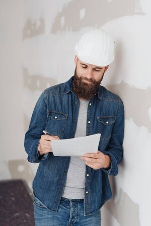 Architect in a hardhat taking notes as he leans against a wall in an unfinished room during renovations smiling quietly to himself