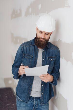 Architekt in einem Bauarbeiterhelm, der sich Notizen macht, während er während der Renovierungsarbeiten an einer Wand in einem unvollendeten Raum lehnt und leise vor sich hin lächelt