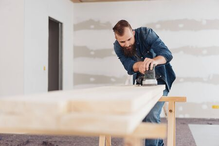 Man sanding planks of wood during renovations to the living room in a home in a low angle view along the wood to him in the background