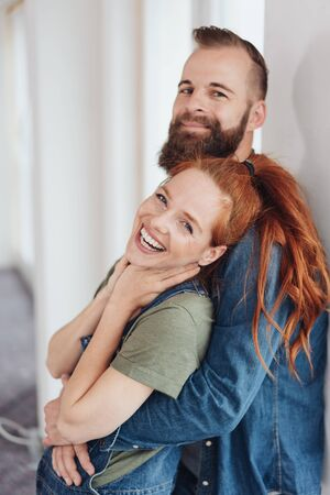 Laughing vivacious redhead woman in her husbands arms turning to smile at the camera as they lean against an interior wall in a close embrace